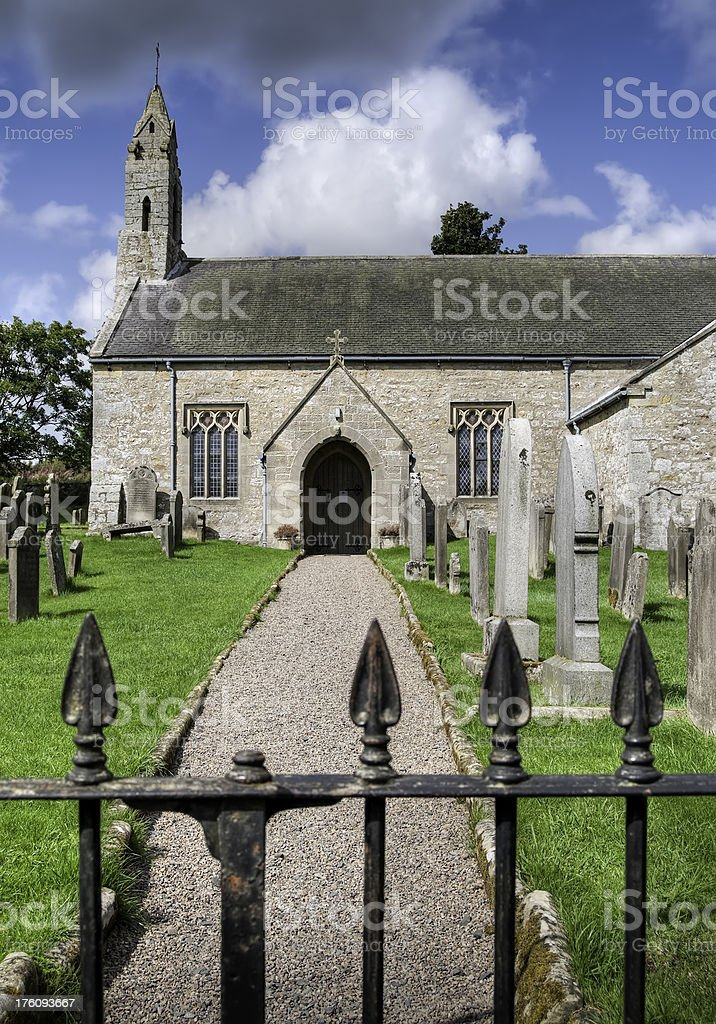 Front of old village church with pathway and iron gate royalty-free stock photo