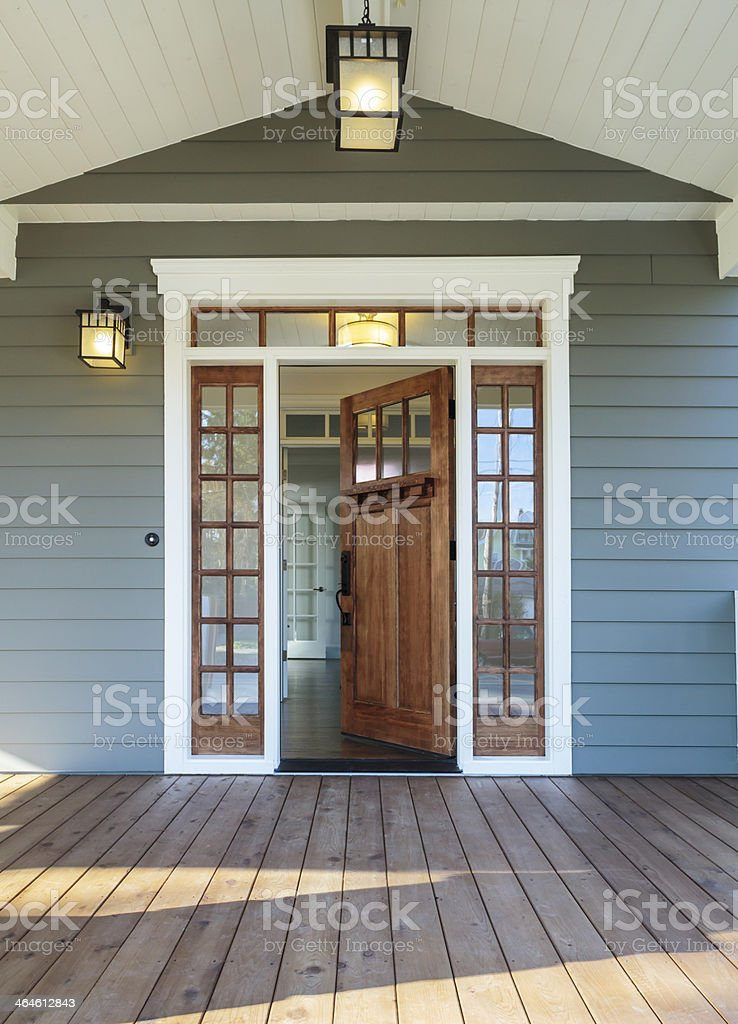 Front porch of blue-gray house with open front door stock photo