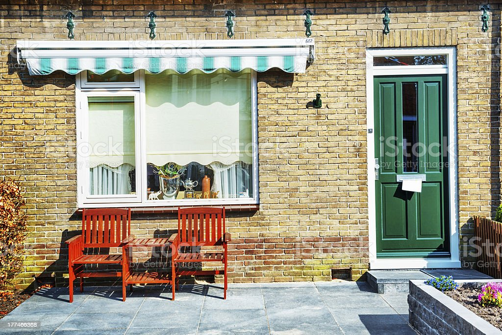 Front Porch of House with Green Door and Wooden Armchairs royalty-free stock photo