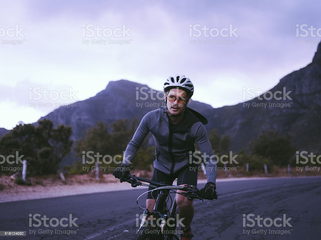 Front shot of cyclist racing along mountain road stock photo