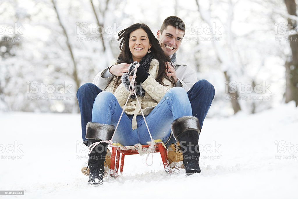 Front view of a beautiful couple sitting on sledge. royalty-free stock photo