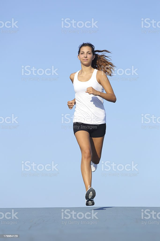 Front view of a beautiful sportswoman running towards camera stock photo