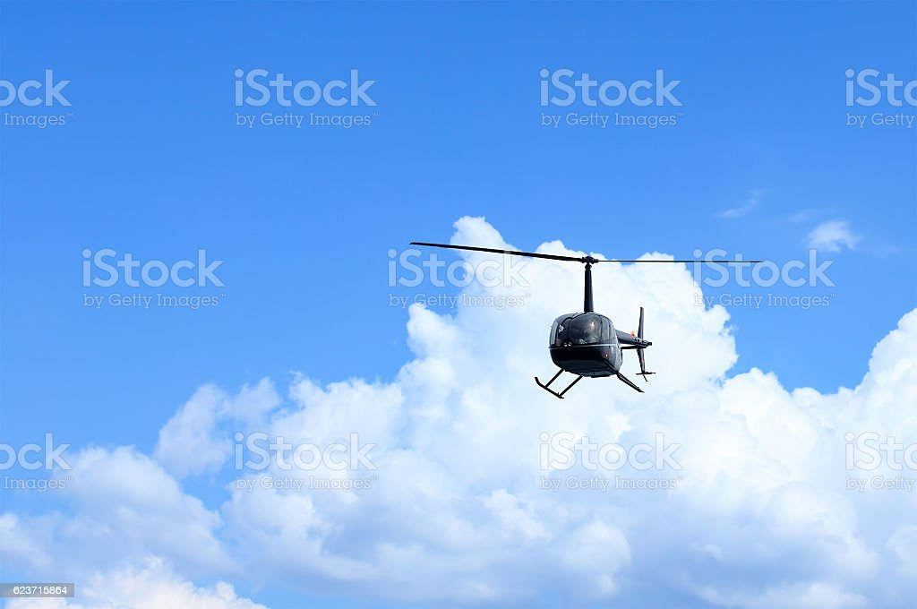 Front view of a black helicopter on blue sky stock photo