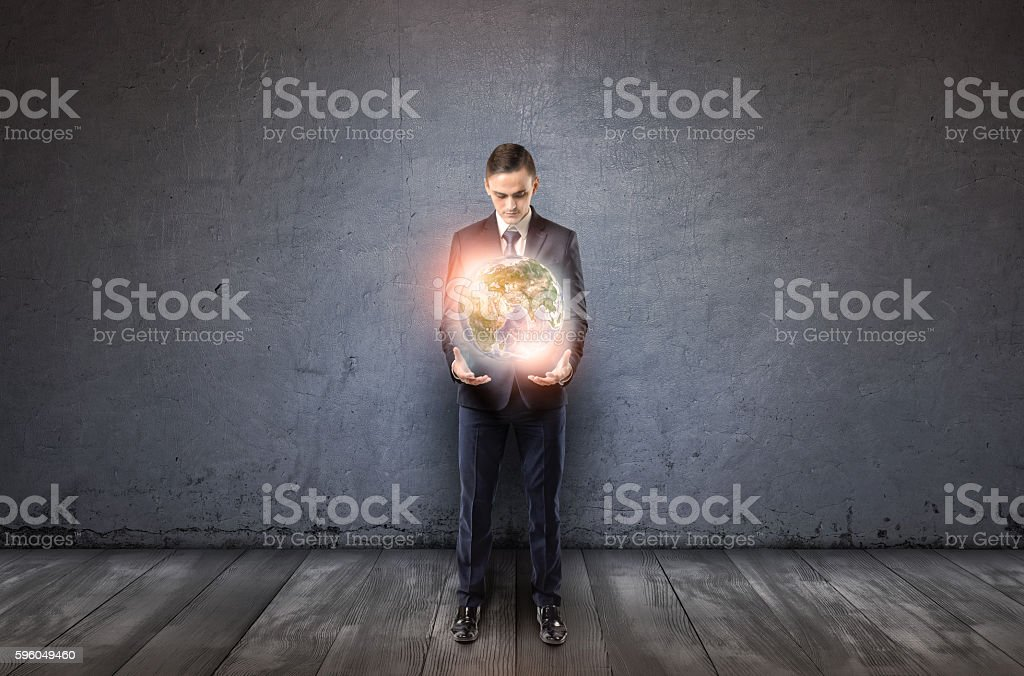 Front view of a businessman holding glowing Earth in his stock photo