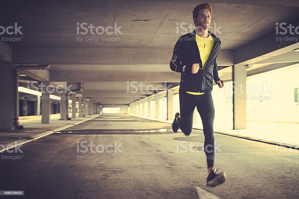 Front view of a young fit man running stock photo