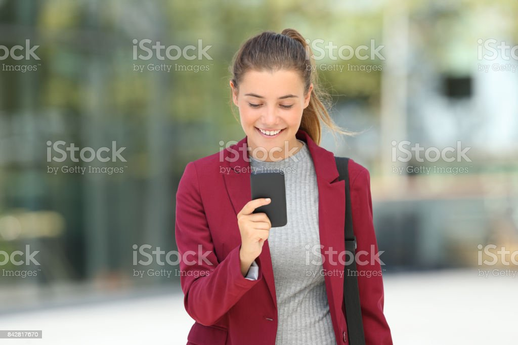 Front view portrait of a single executive reading phone messages and...