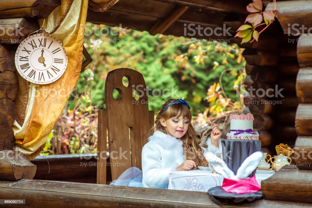 Front view of an little beautiful girl holding a piece of cake on a spoon at the table stock photo