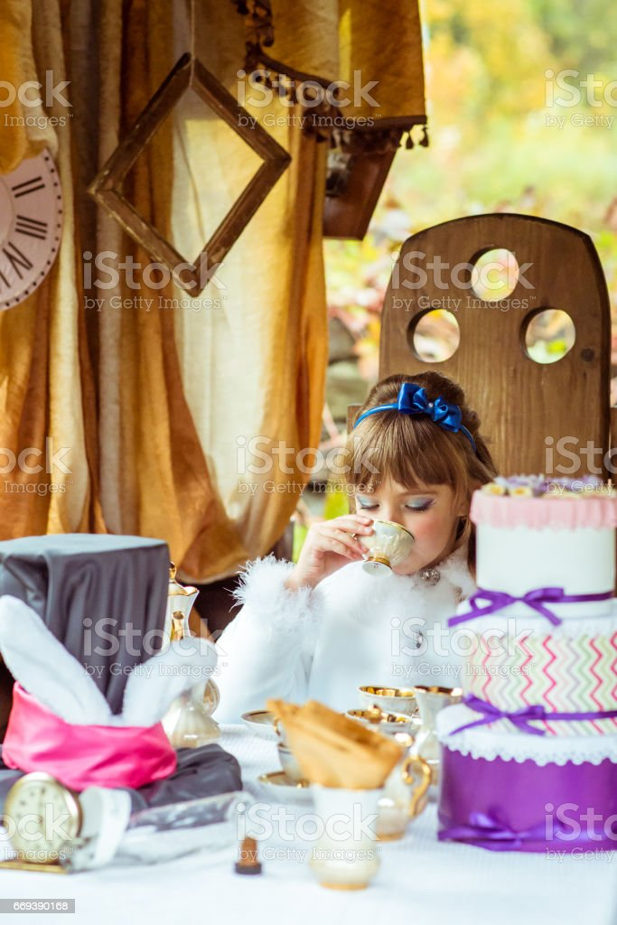 Front view of an little beautiful girl in the scenery of Alice in Wonderland drinking a tea at the table in the park stock photo