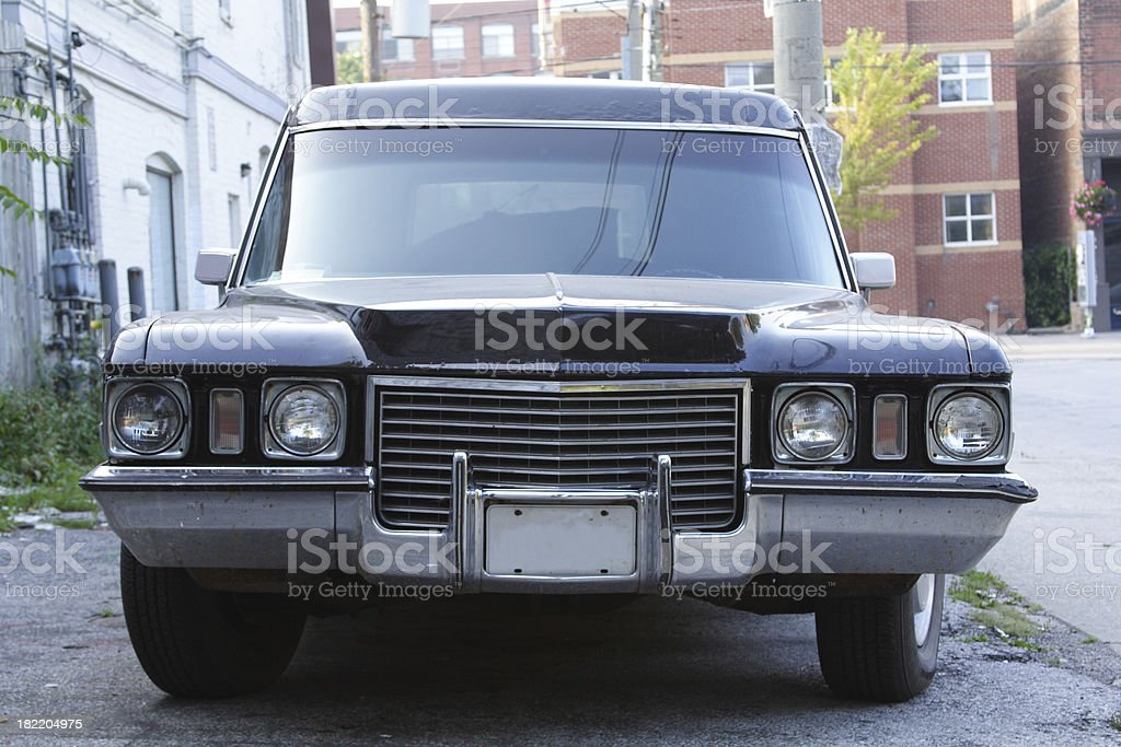 Front View of Black 1972 Cadillac Hearse Parked In Alley stock photo