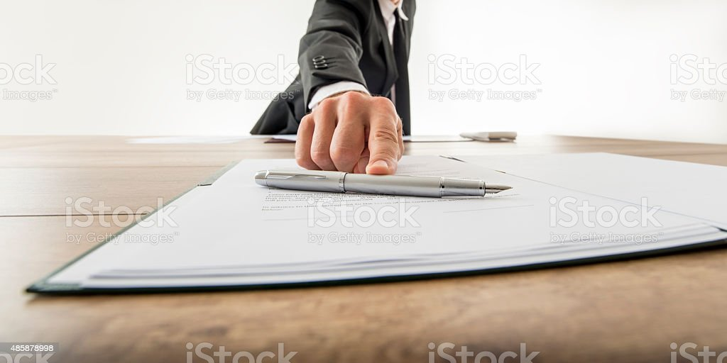 Front view of businessman offering you to sign a document stock photo
