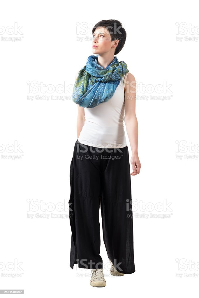 Front view of confident fashion model walking forward looking up stock photo