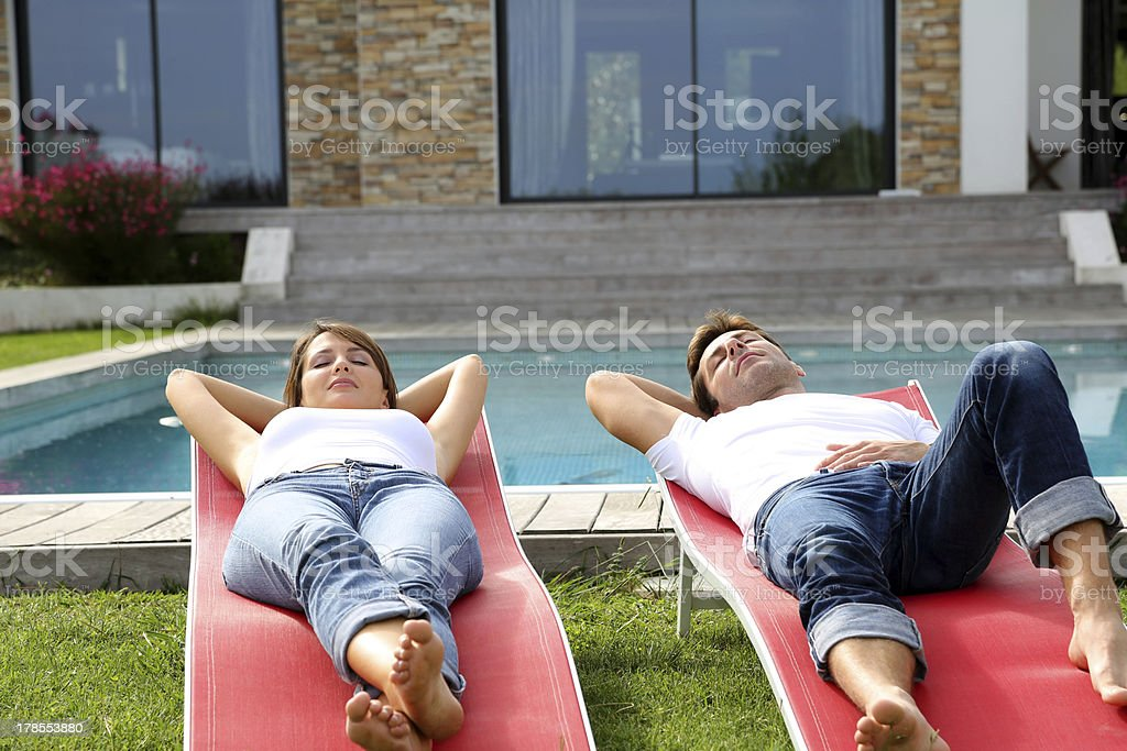 Front view of couple relaxing in long chairs by pool stock photo