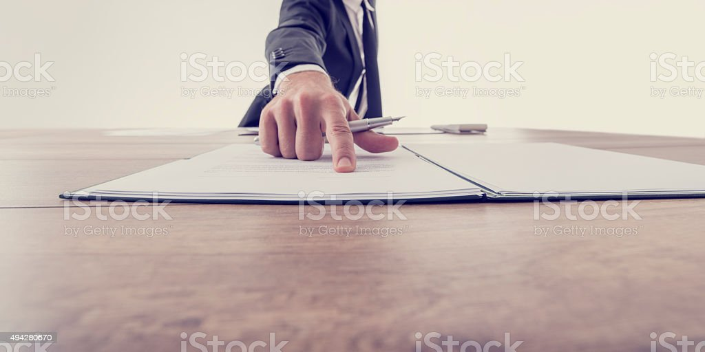 Front view of employer pointing to a contract stock photo