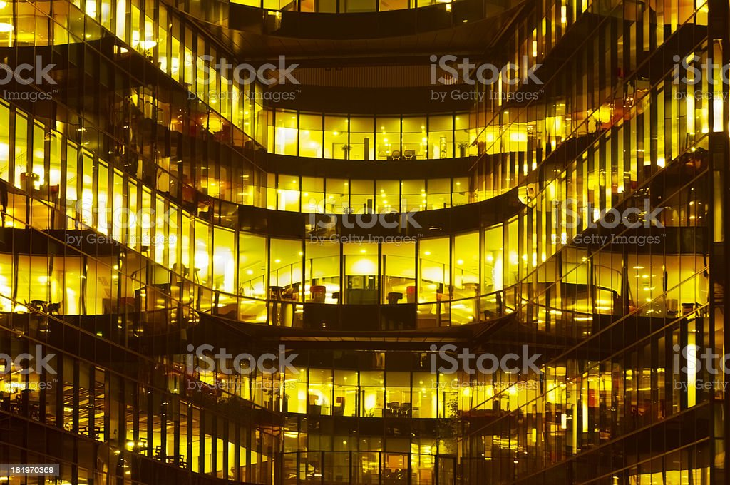 Front View of  Glass Office Building Illuminated at Night royalty-free stock photo