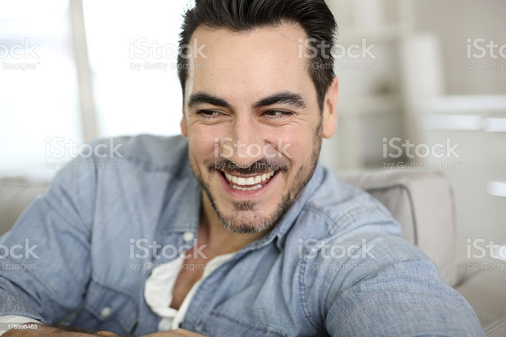 Front view of happy man sitting on a couch royalty-free stock photo