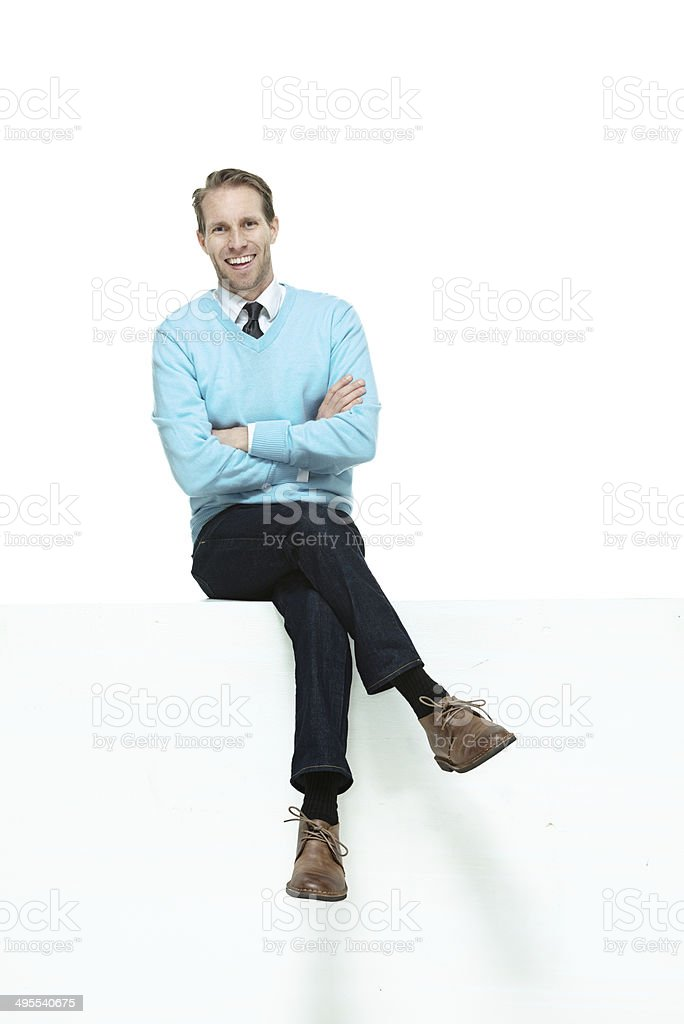 Front view of happy man sitting on ledge stock photo