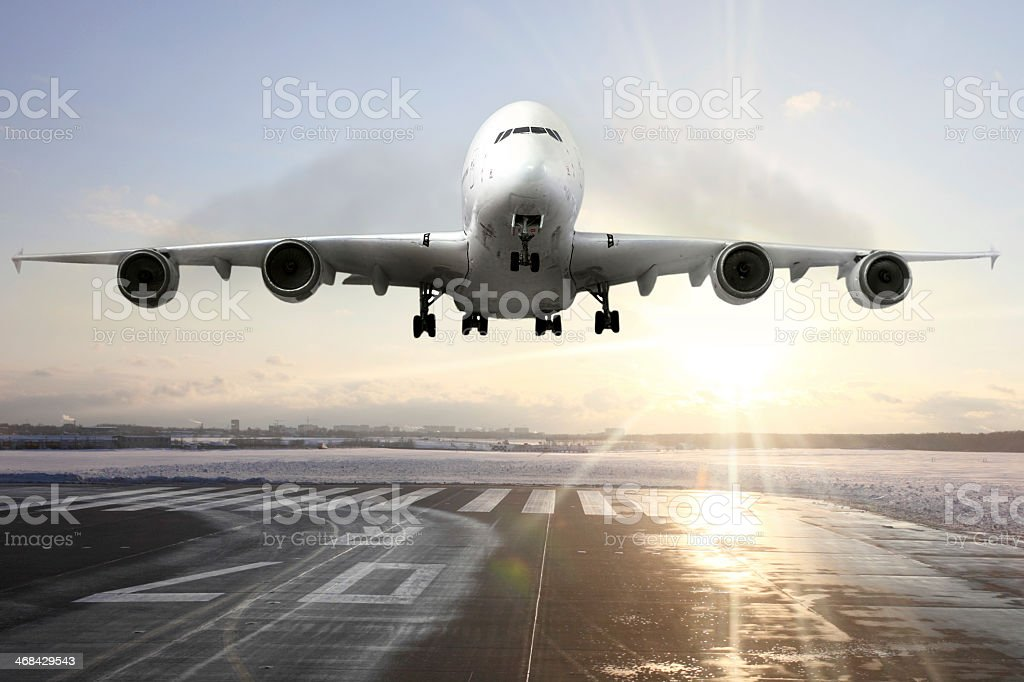 Front view of landing passenger airplane at sunset stock photo