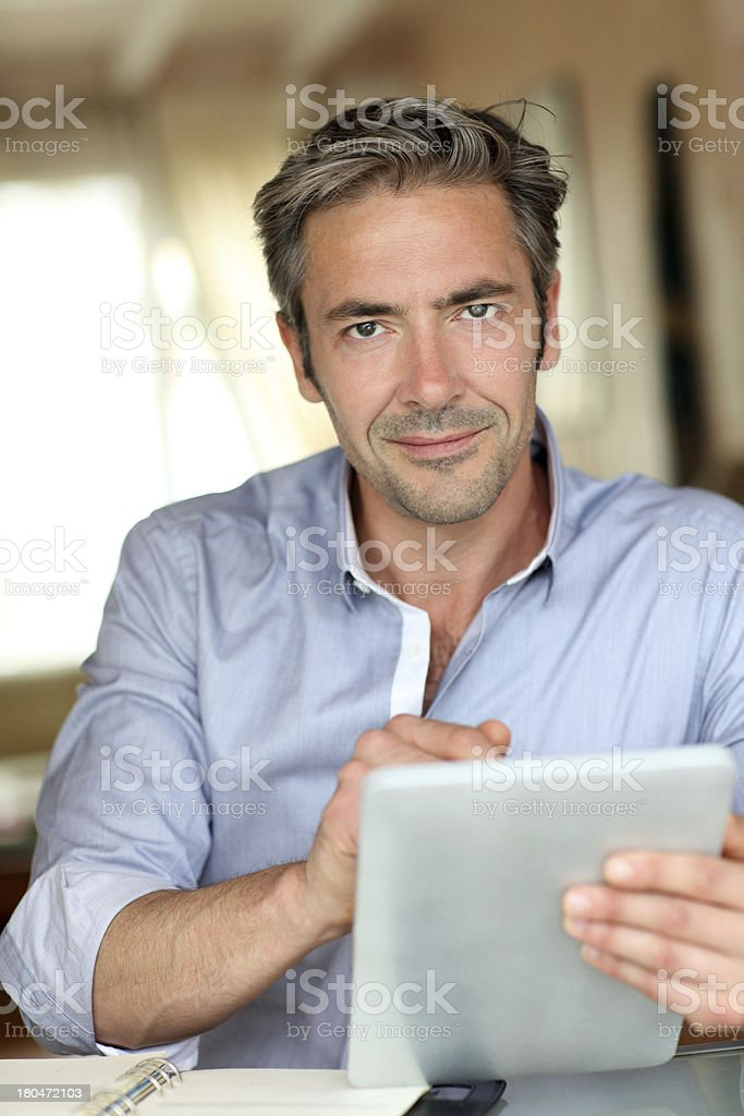 Front view of mature man using tablet to work royalty-free stock photo