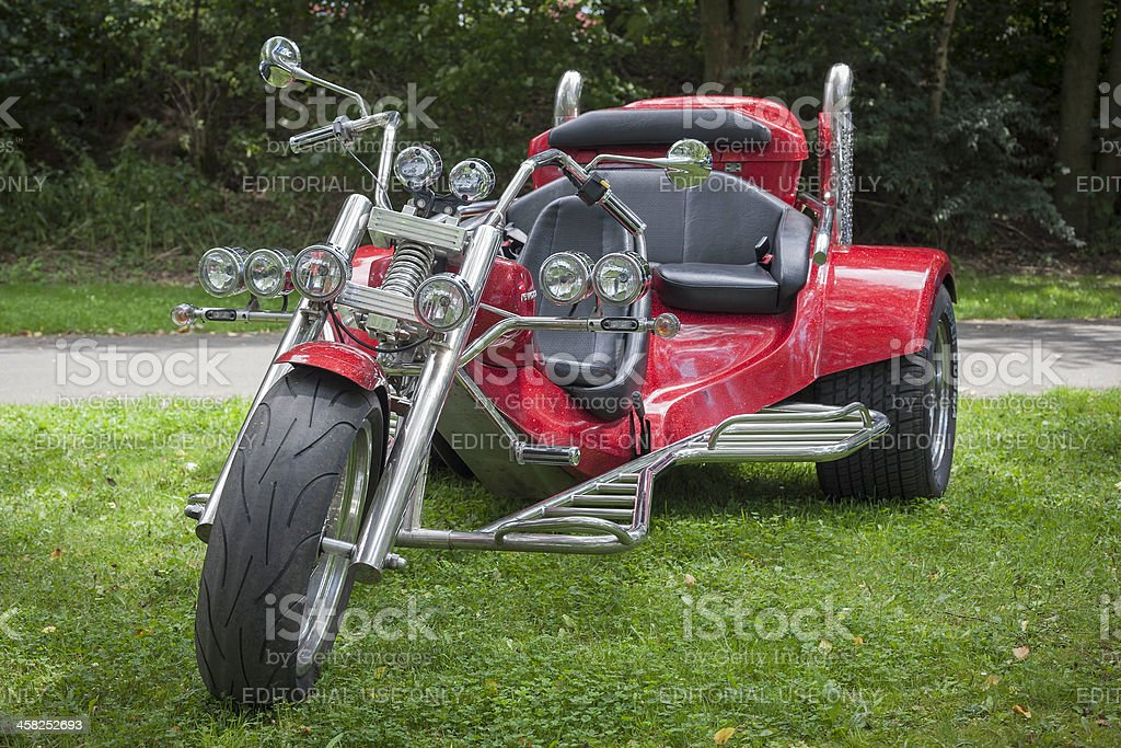 Front view of red motorized trike parked on grass stock photo