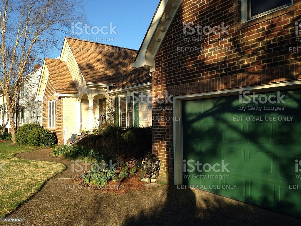 Front view of residential brick and vinyl home stock photo