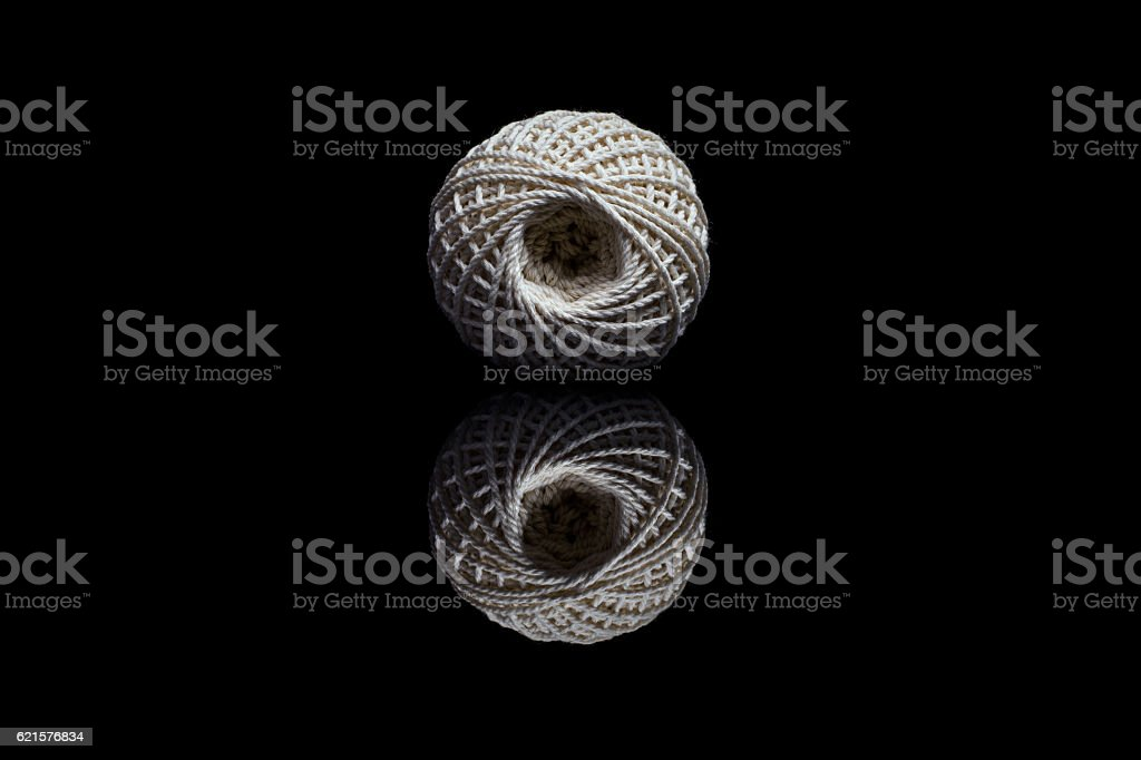 Front view of white ball of string on black background stock photo