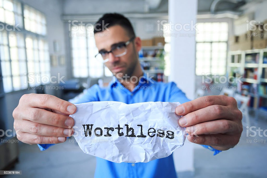 Front view of young man holding a sign 'worthless' stock photo