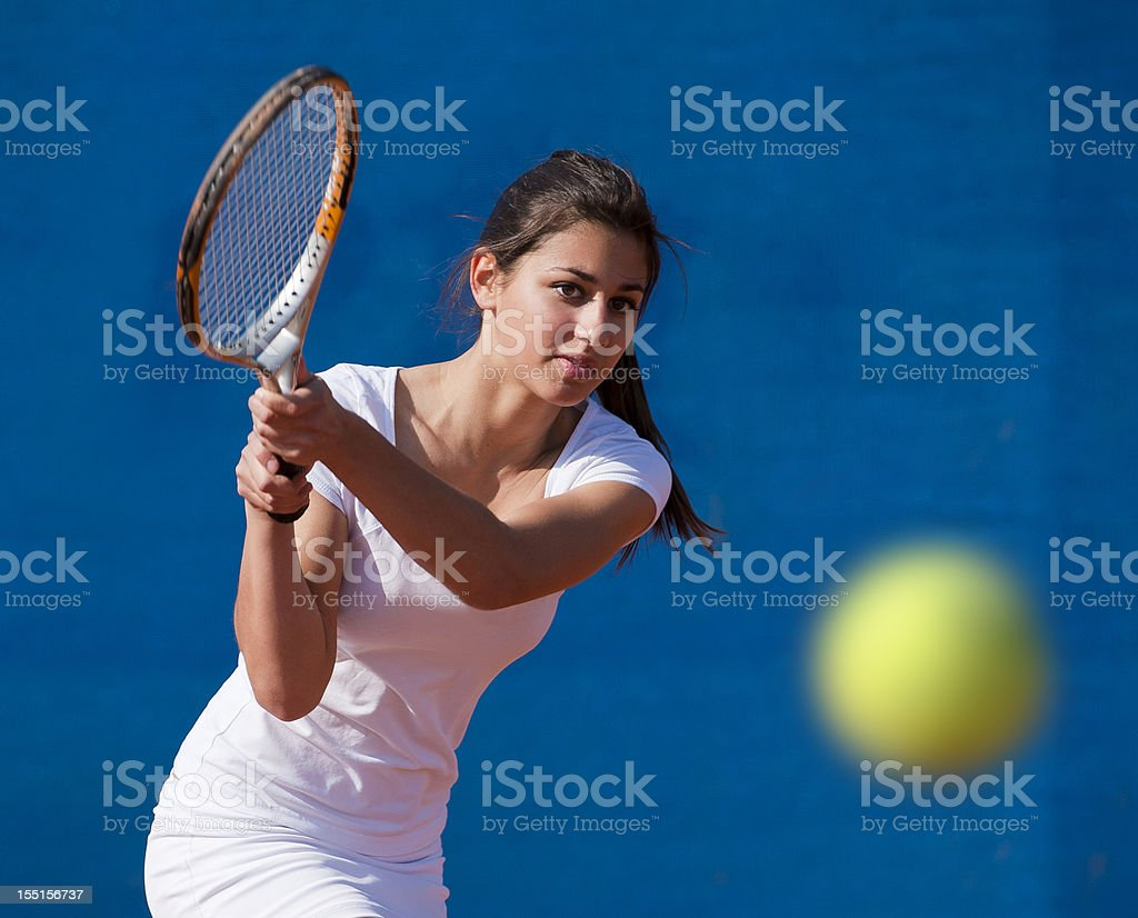 Front view of young woman playing tennis stock photo