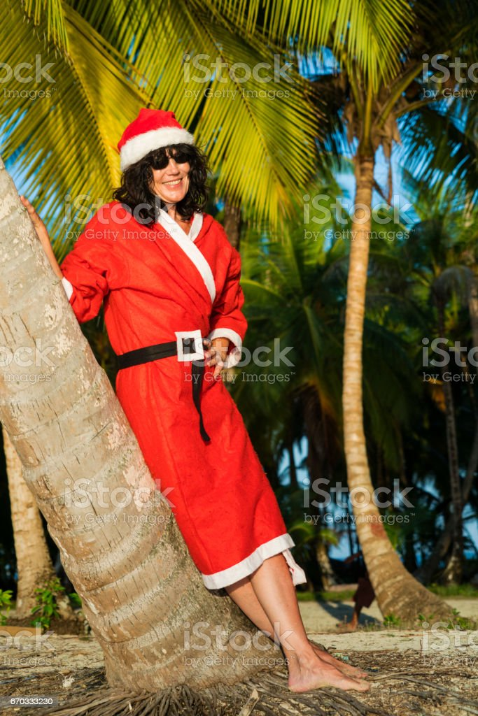 Front view portrait of Santa Claus woman with long hair and sun glasses, leaning against palm tree on beach  of Naranjo Chico Island in Caribbean See stock photo