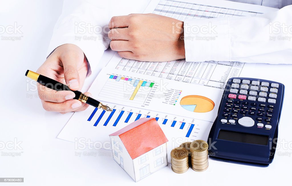 Front views of Hand people holding fountain pen on business chart and calculator with coins stack and house paper for loans concept stock photo