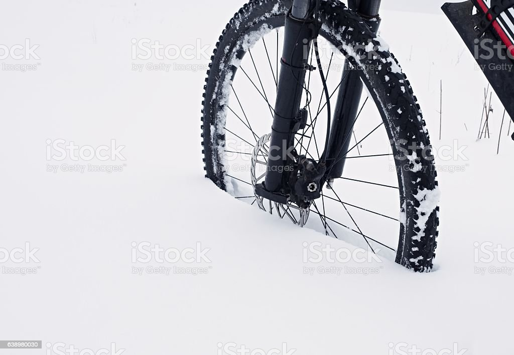 Front wheel of mountain bike in powder snow. Lost path stock photo