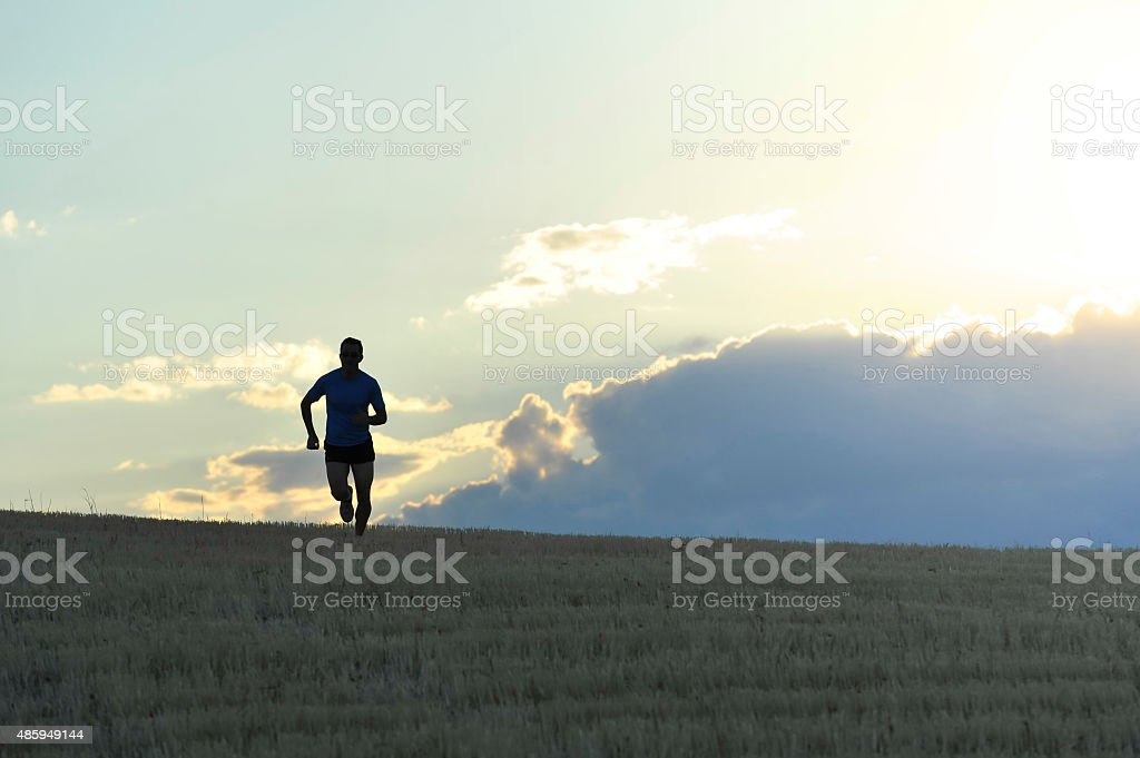 frontal silhouette of man running in countryside in summer sunset stock photo
