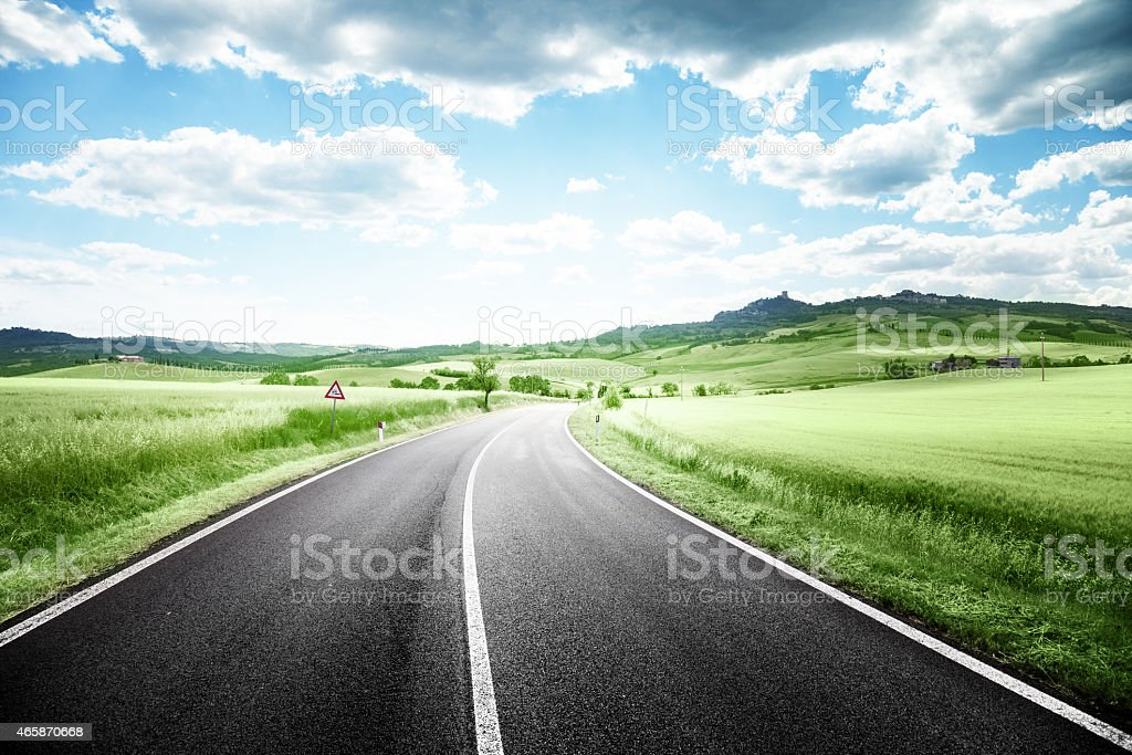 Frontal view of a winding asphalt road in Tuscany, Italy stock photo