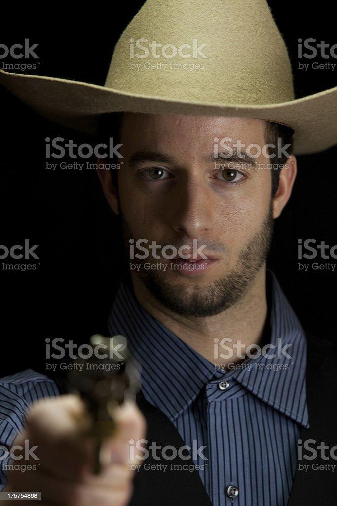 front-view of cowboy with gun (low-key studio shot) stock photo