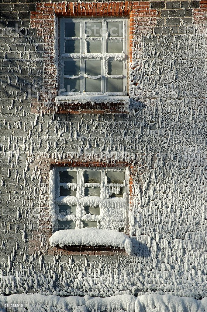Frost and rime ice covered windows and brick wall stock photo