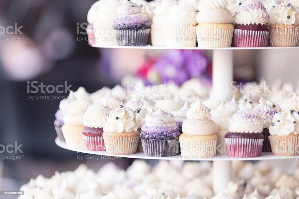 Frosted Mini Cupcakes Displayed on Tiered Cake Stand stock photo