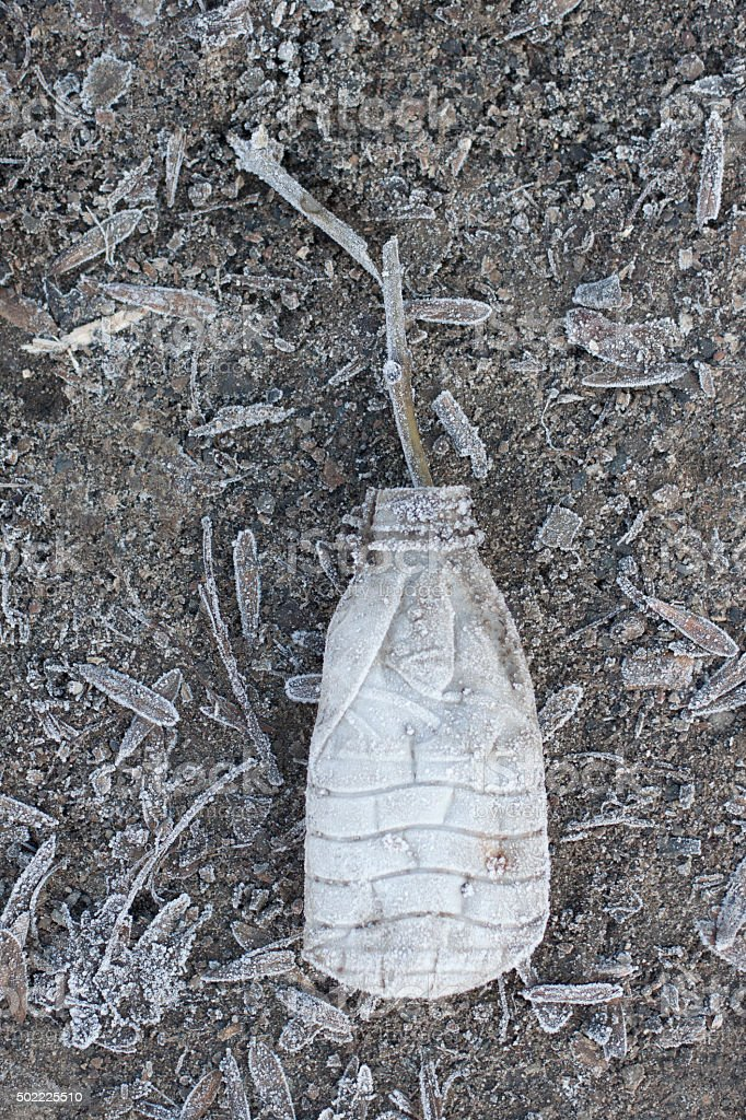 Frosted plastic bottle on the ground stock photo