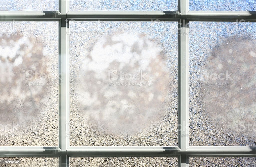 A frosted window pane and its glass with condensation stock photo