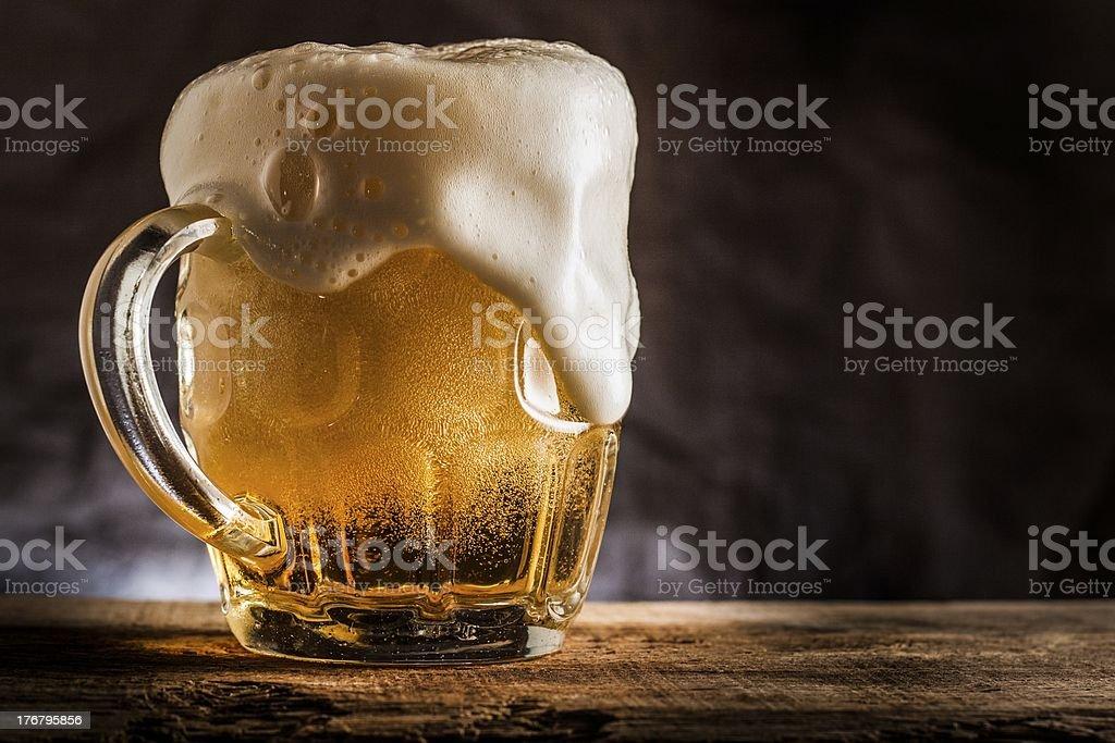 Frosty foaming mug full of beer stock photo
