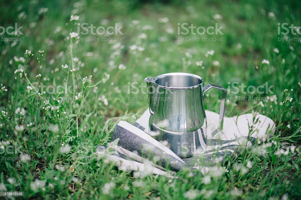 Frothing milk pitcher on the green background stock photo