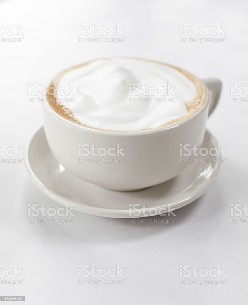 A frothy cappuccino in a white coffee cup stock photo