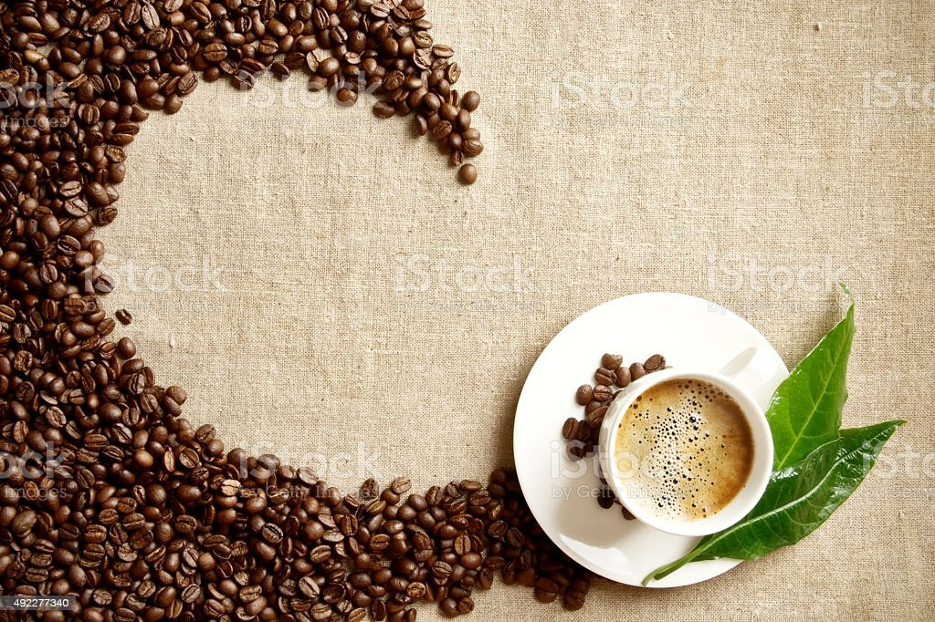 Frothy coffee cup, beans,leaf twisted in swirl on flax stock photo