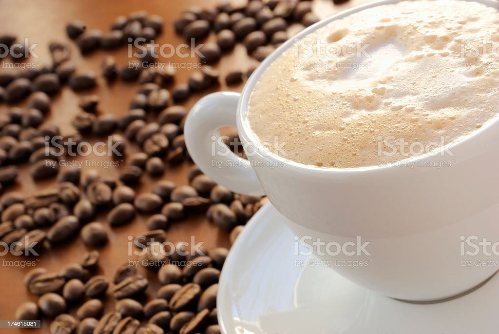 Frothy coffee in a white teacup and saucer by coffee beans royalty-free stock photo