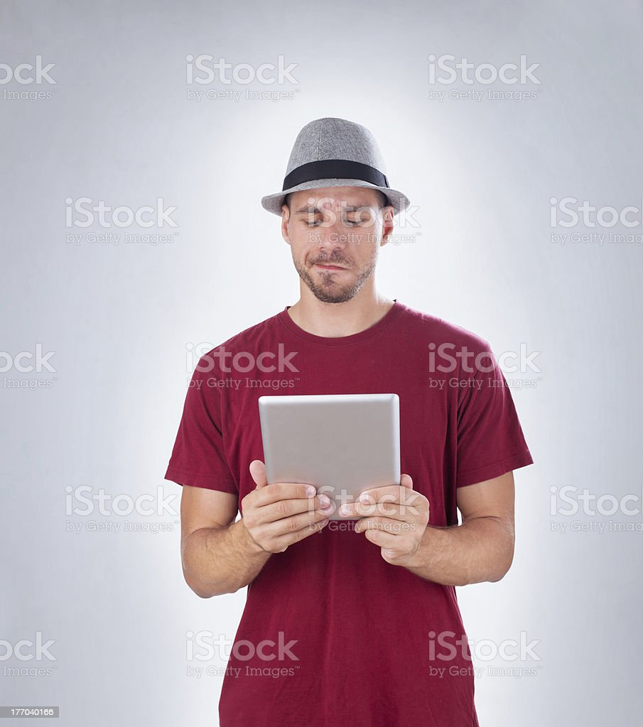 Frowned man confusedly looking at  tablet PC, copy space royalty-free stock photo
