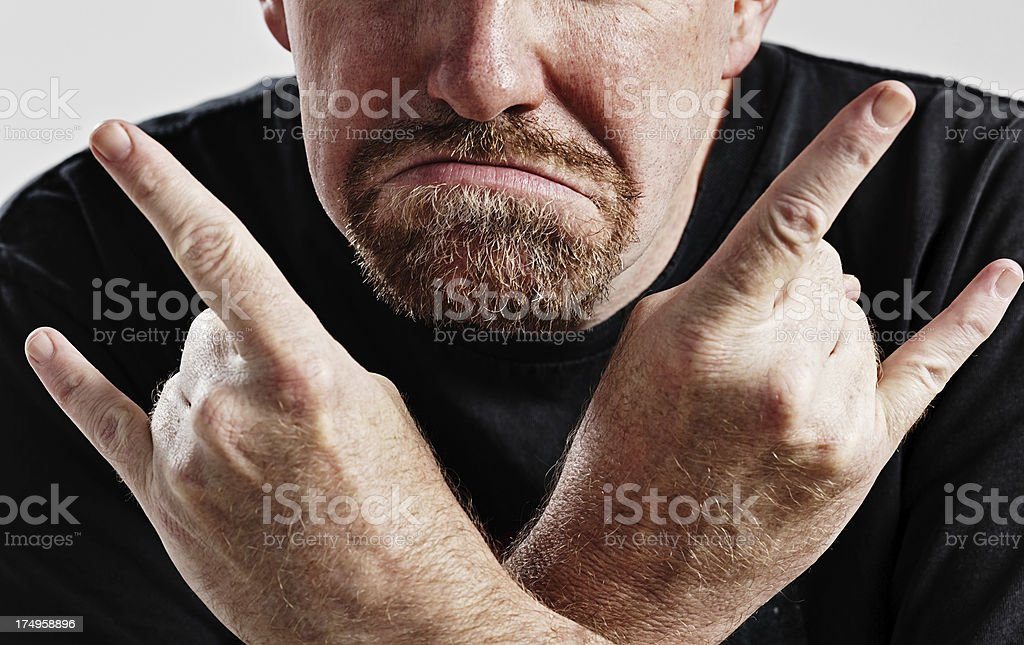 Frowning aging rocker makes Rock-and-Roll devil horns gesture stock photo