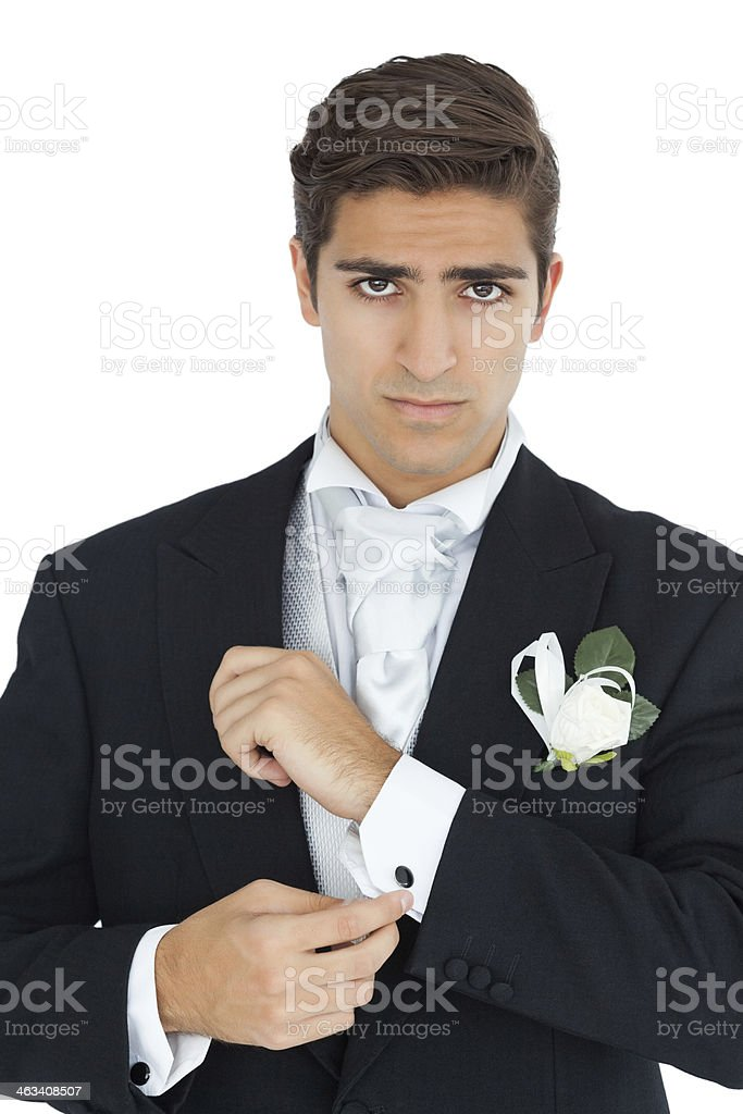 Frowning attractive young groom buttoning his cufflinks stock photo
