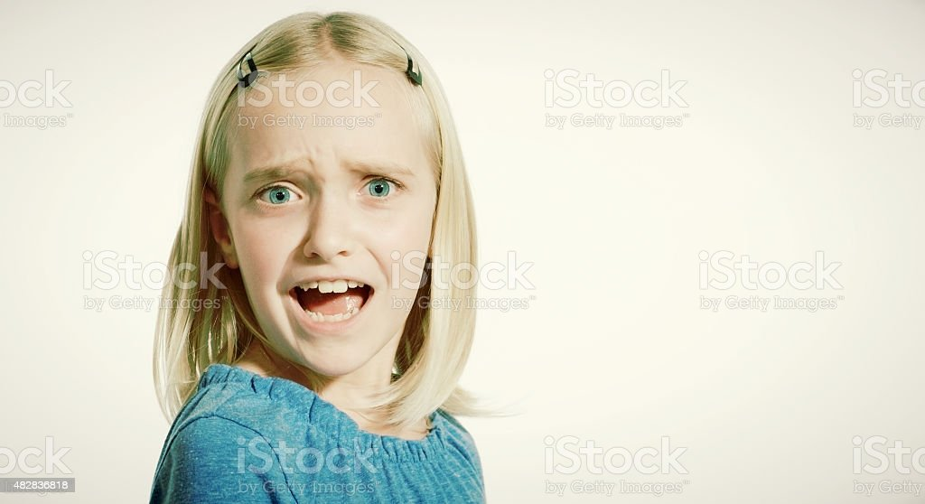 Frowning blonde 9-year-old girl frowns, alarmed by something or someone stock photo