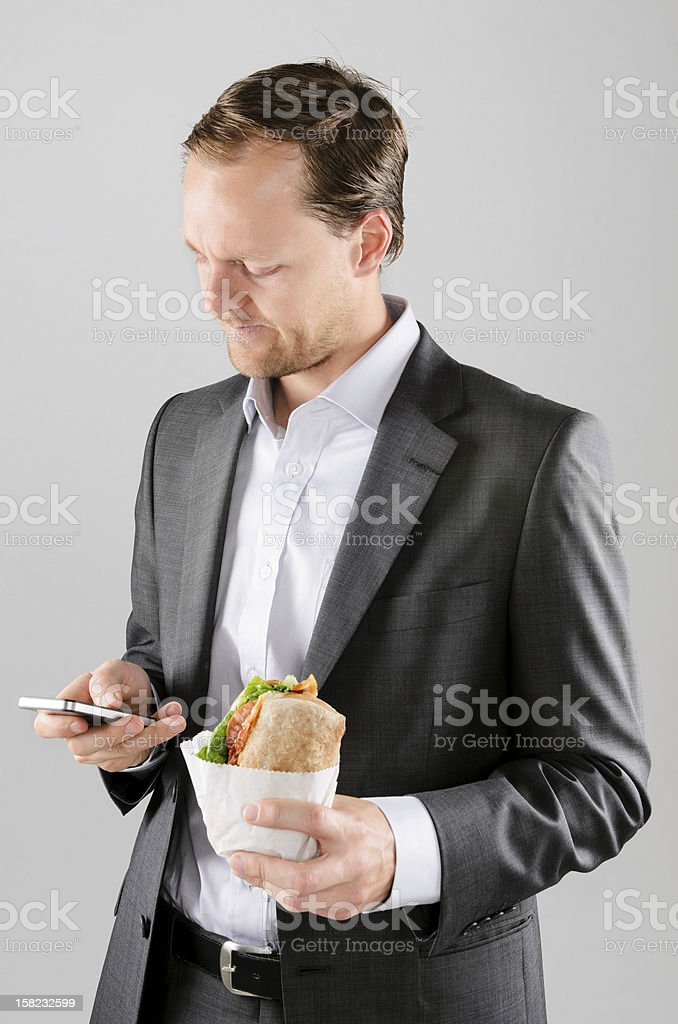 Frowning business man with lunch and mobile phone stock photo