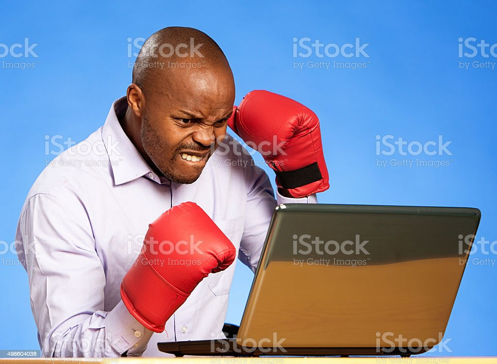 Frowning, frustrated businessman in boxing gloves fights his laptop stock photo