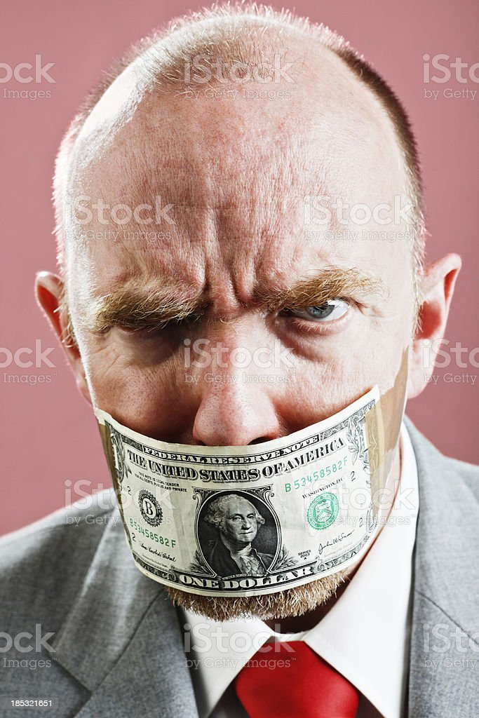 Frowning furious businessman gagged with US dollar bill stock photo
