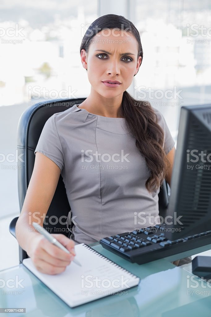 Frowning gorgeous businesswoman writing stock photo